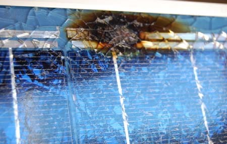 burn mark and shattered glass on front of panel